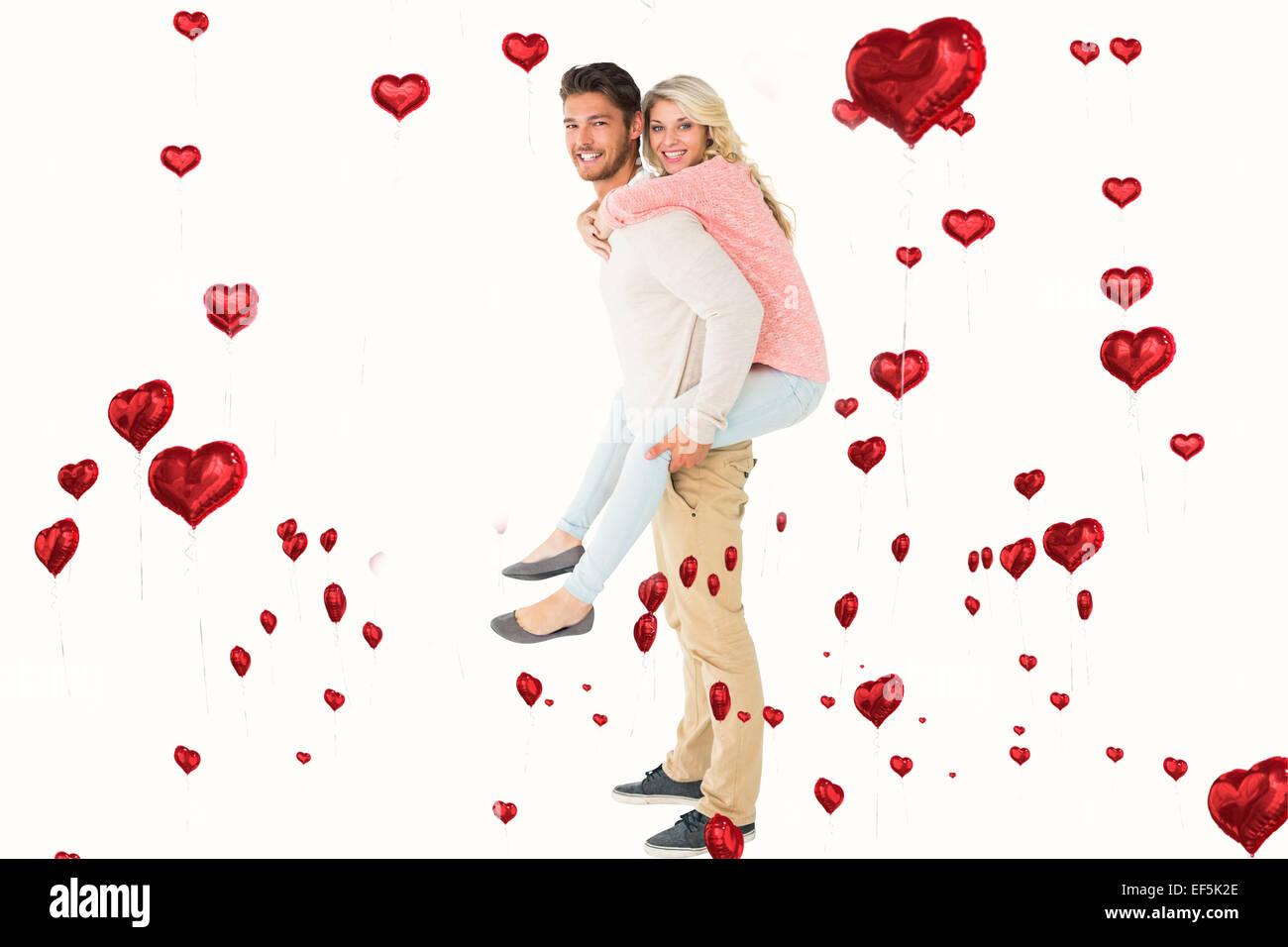 Composite image of handsome man giving piggy back to his girlfriend - Stock Image
