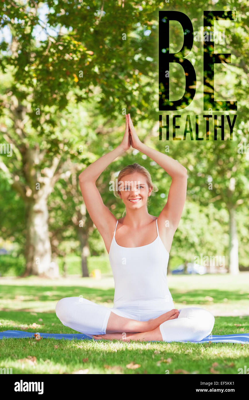 Composite image of cute young woman doing yoga sitting on an exercise mat - Stock Image