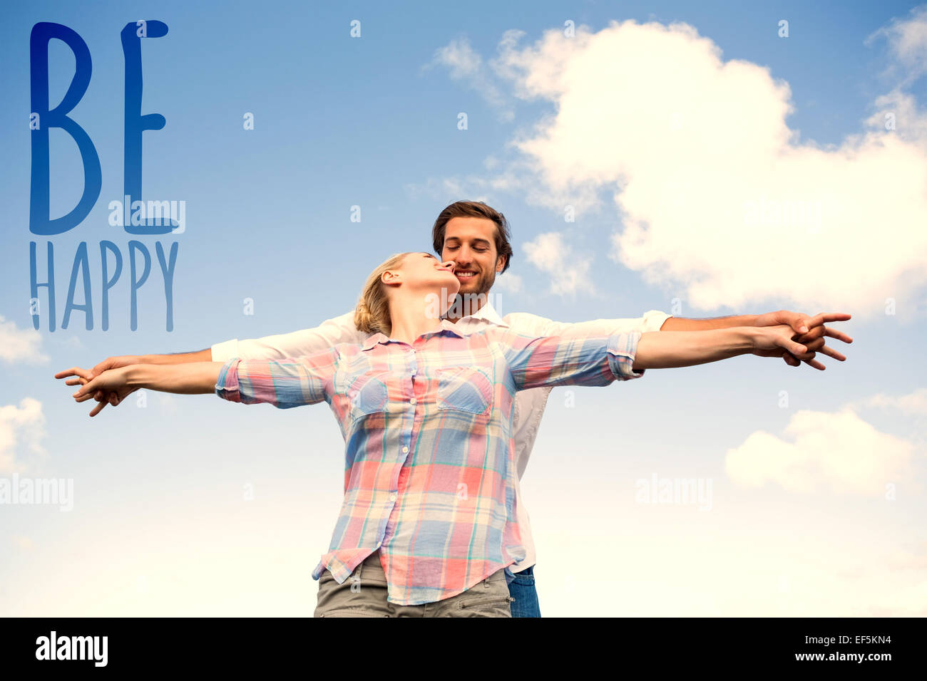 Composite image of happy couple standing outside with arms stretched kissing Stock Photo