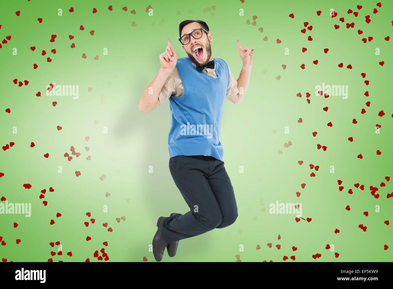 Composite image of geeky hipster jumping and smiling - Stock Image