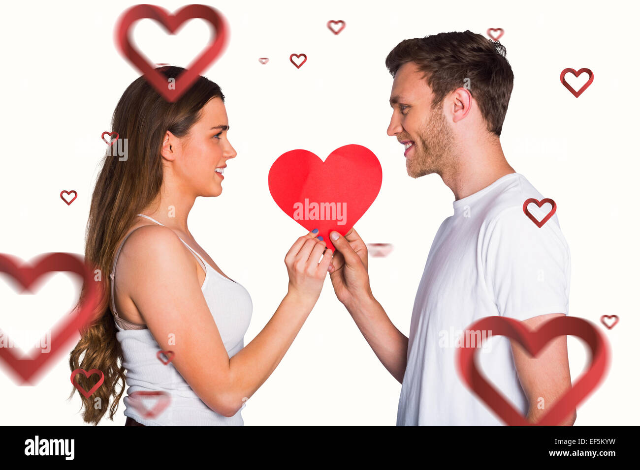 Composite image of romantic young couple holding heart - Stock Image