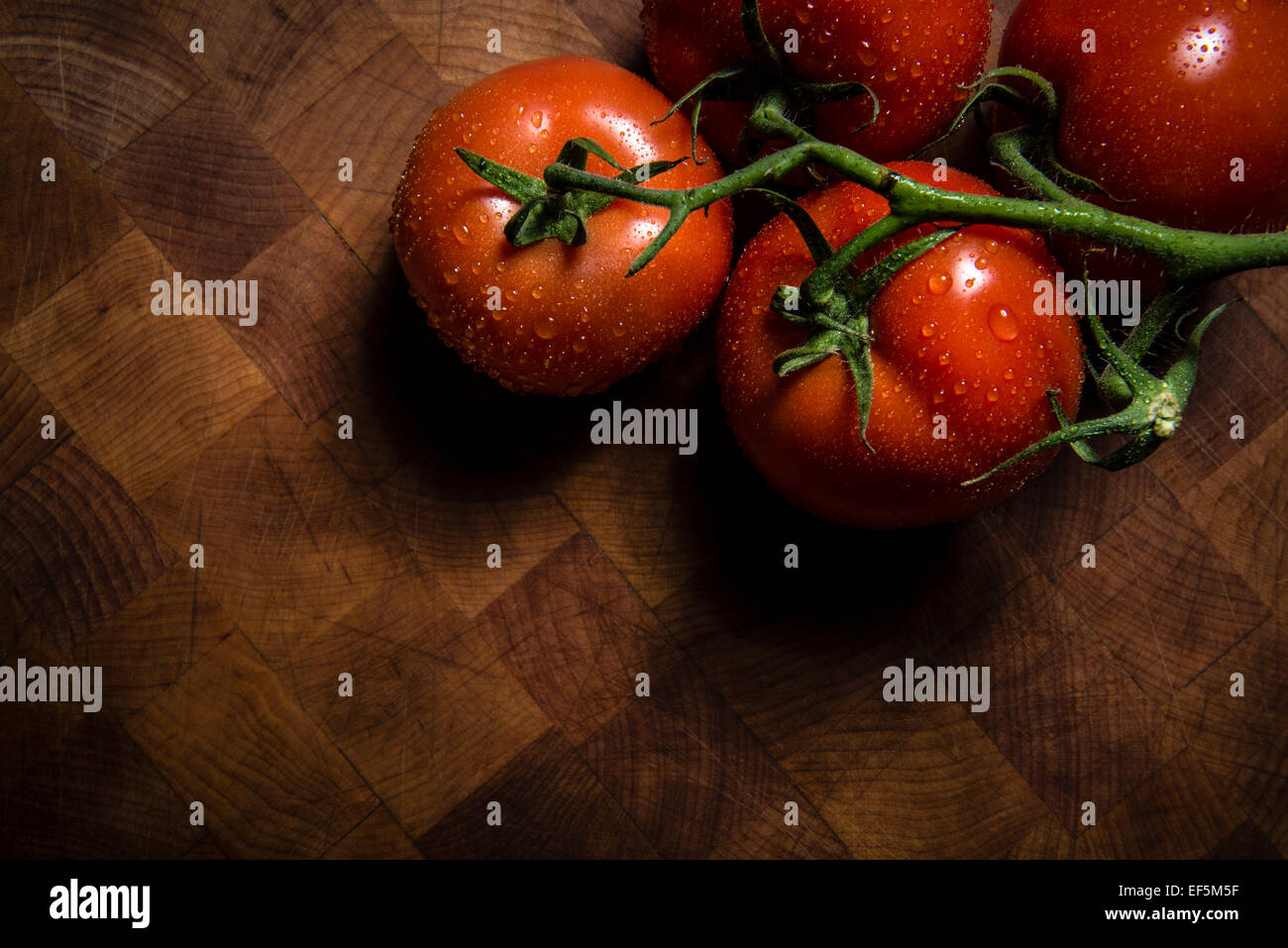 Wet tomatoes on a chopping board - Stock Image
