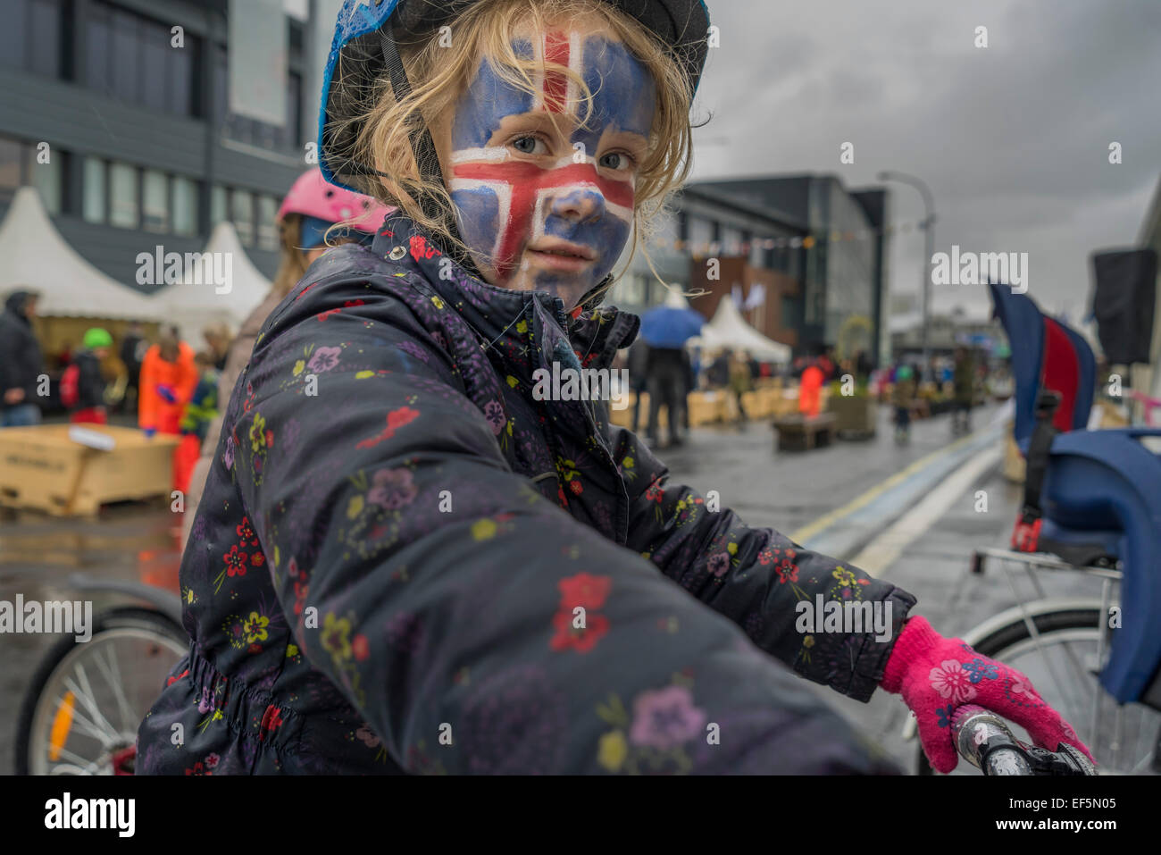 Girl with her face painted with the Icelandic flag, summer festival, Reykjavik, Iceland - Stock Image