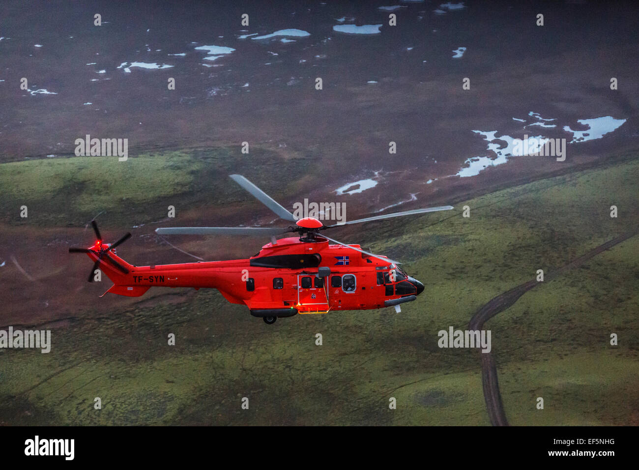 Aerial view-TF-SYN, Search and Rescue Helicopter flying by Gullfoss Waterfalls, Iceland. - Stock Image