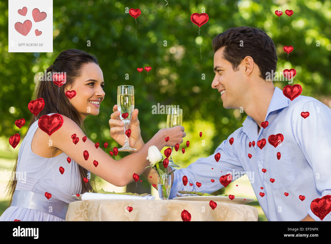 Composite image of couple with champagne flutes sitting at outdoor café Stock Photo