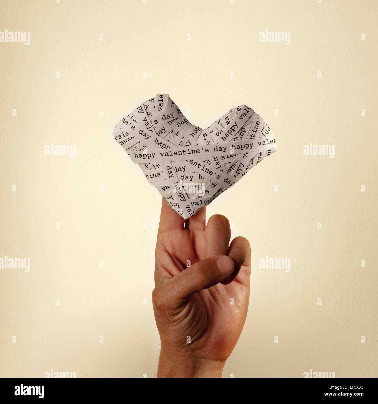 the hand of a young man holding a heart made-up with paper strips with the text happy valentines day, with a retro - Stock Image