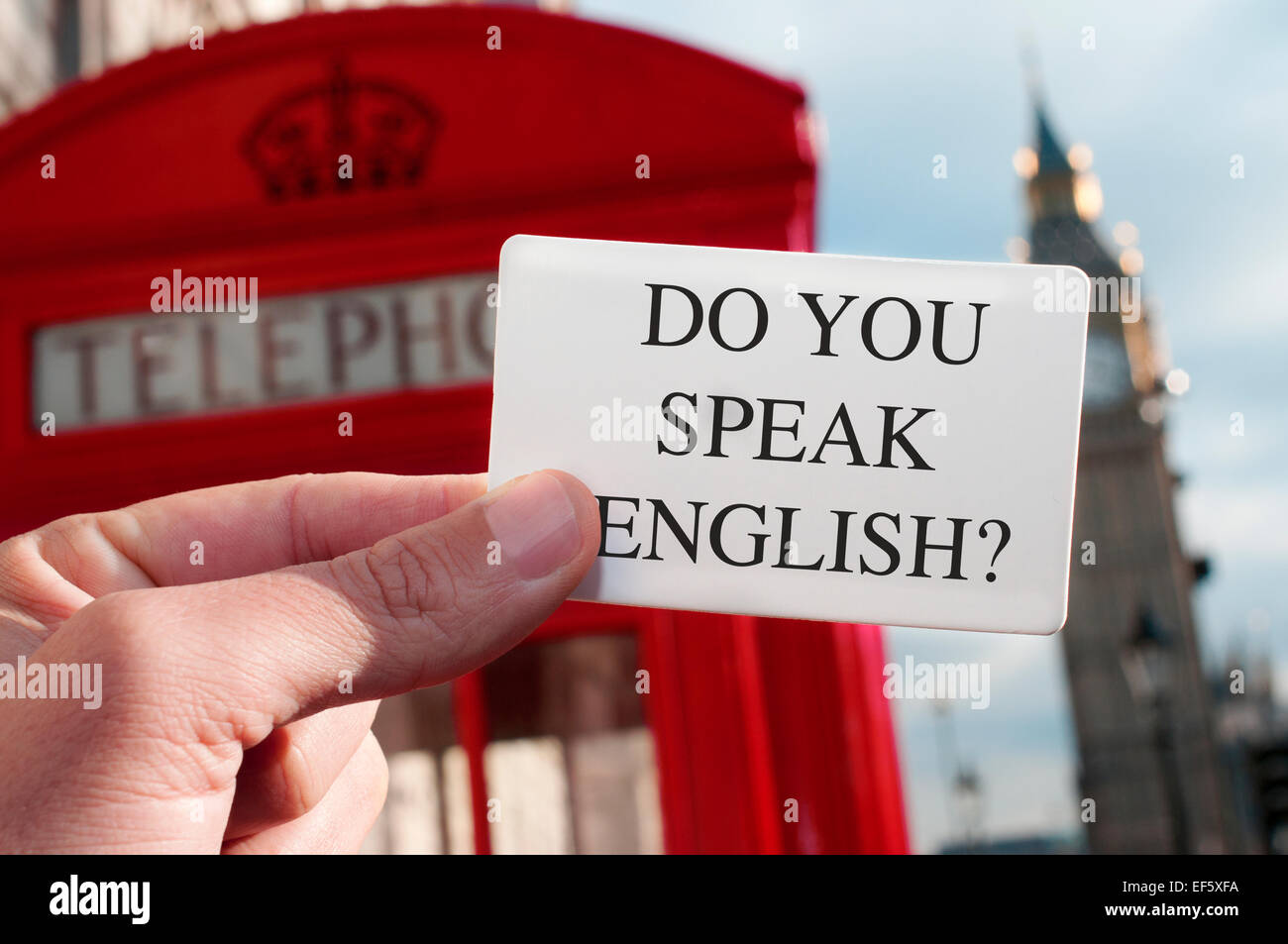 a man holding a signboard with the text do you speak english? with a red telephone booth and the Big Ben in the - Stock Image