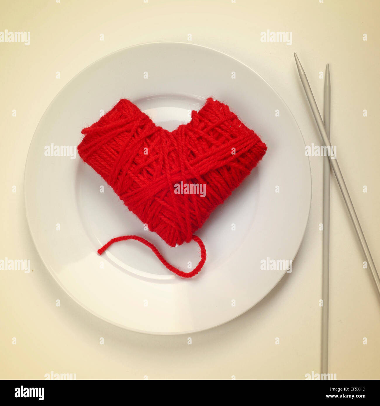 a heart-shaped ball of yarn in a plate and knitting needles at the side, as the flatware, with a retro effect - Stock Image