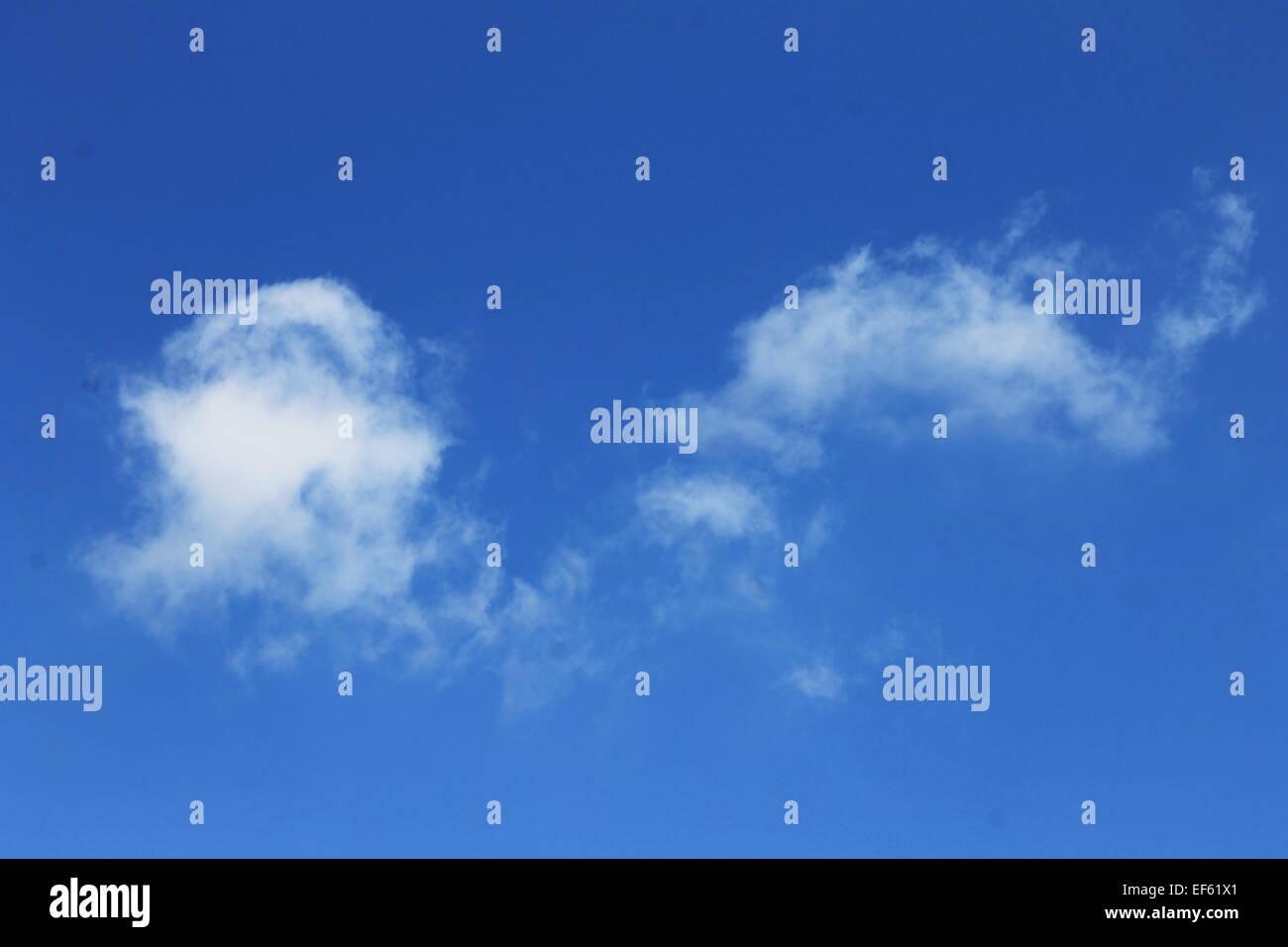 A single white cloud on a clear blue sky - Stock Image