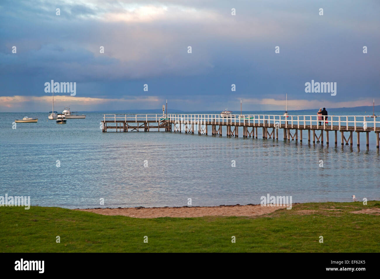 Couple watching sunset from wooden jetty at seaside resort Sorrento in the Port Phillip Bay, Victoria, Australia - Stock Image