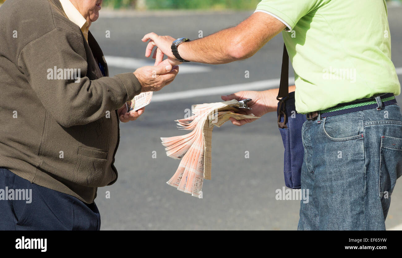 Elderly Spanish man buying Lotto ( Lottery ticket ) from official seller in village in Spain - Stock Image