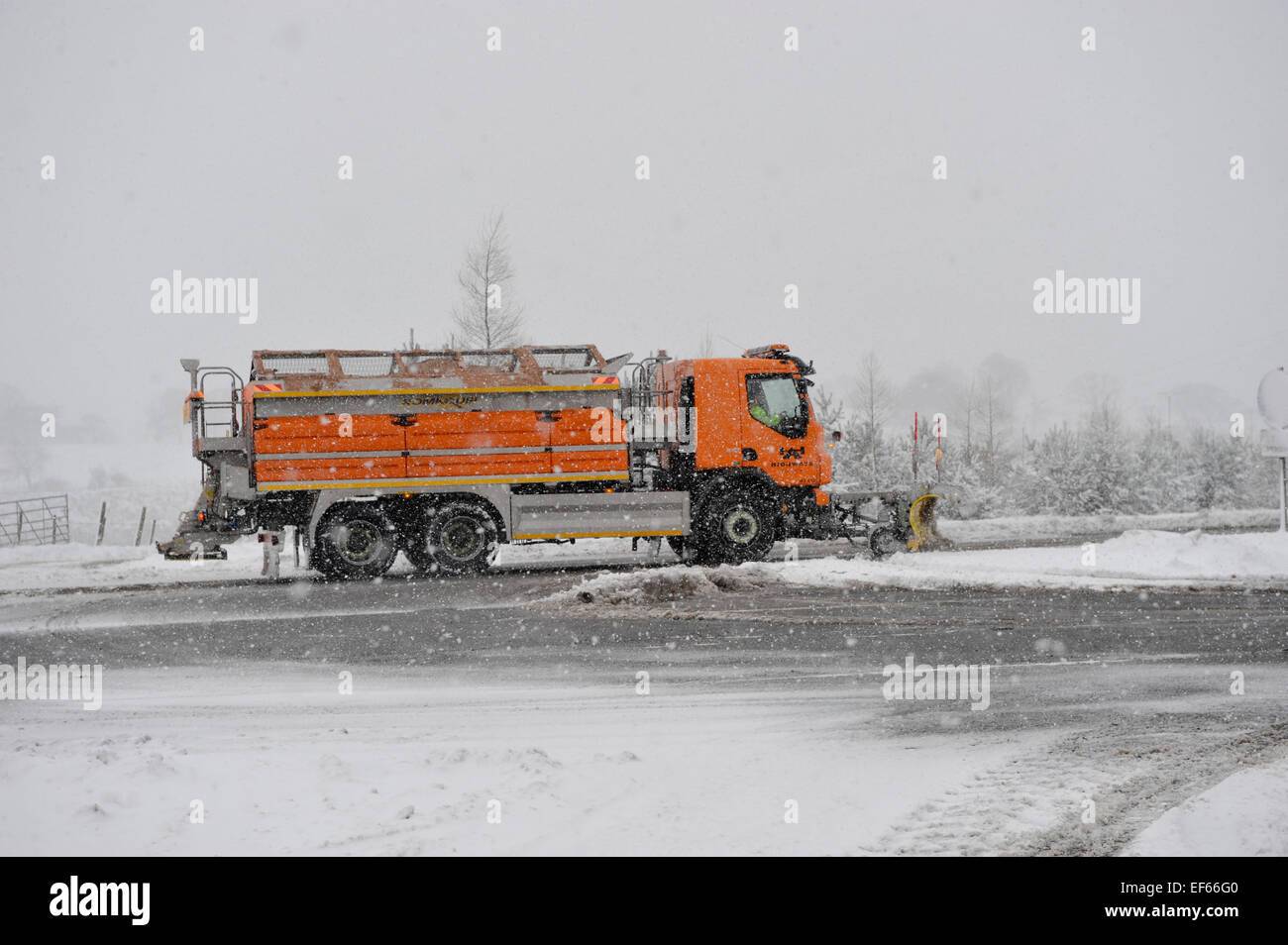 Council wagon spreading grit and snowploughing a snow covered road, Cumbria, UK - Stock Image