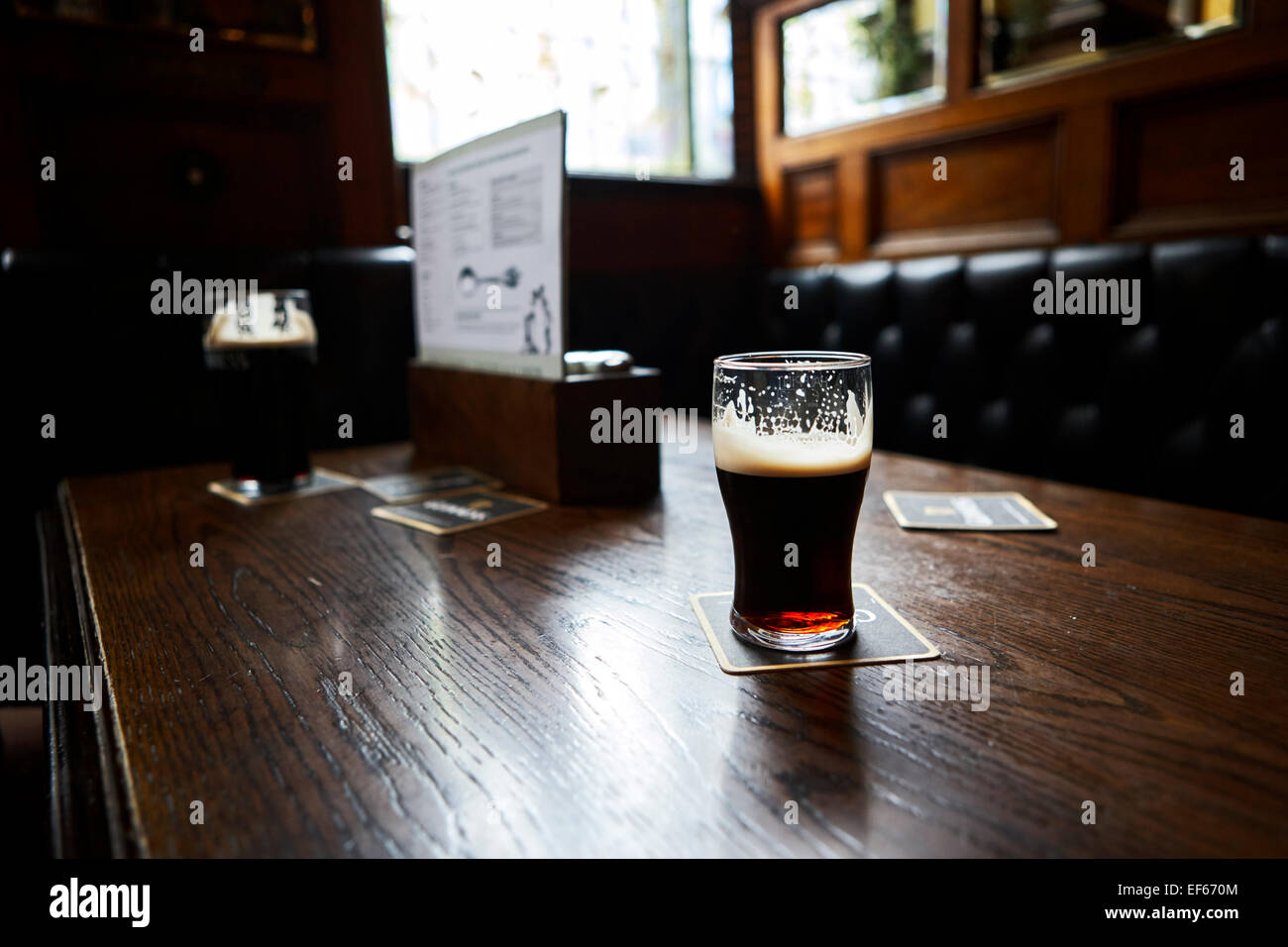 half drunk pint of guinness in an old irish pub - Stock Image