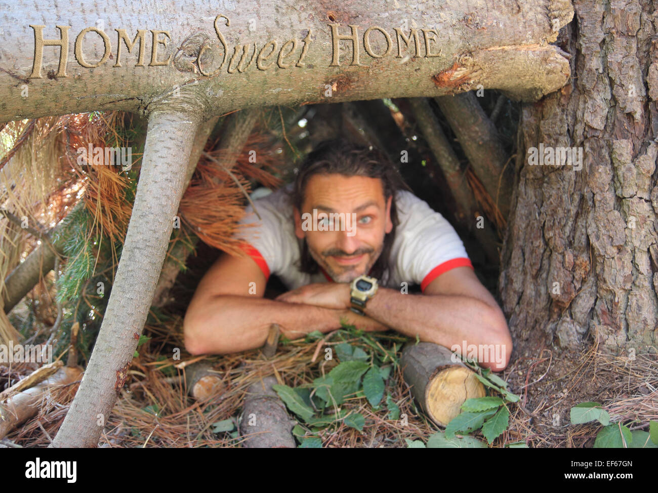 smiling out of focus man in the wild under Home sweet Home sign - Stock Image