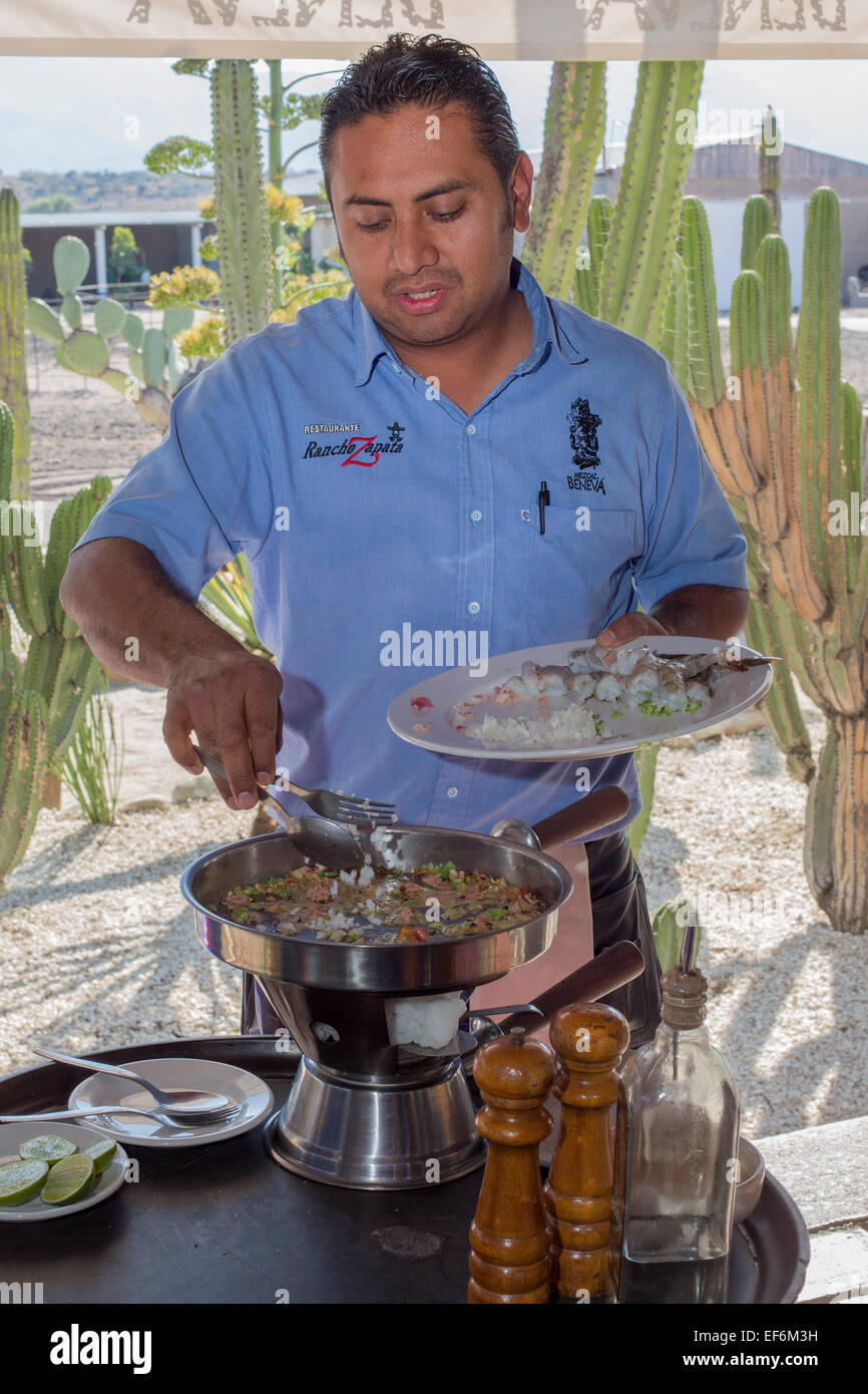 Mitla, Oaxaca, Mexico - A waiter cooks a shrimp dish for diners at Restaurante Rancho Zapata. - Stock Image