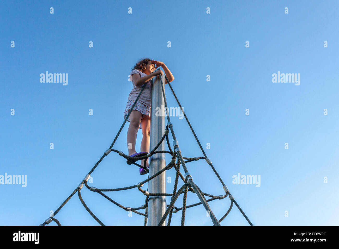 Confident nine year old girl on top of a climbing frame. - Stock Image