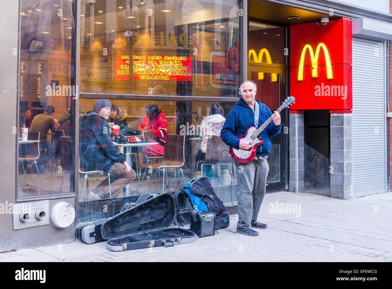 Guitarist busking outside McDonalds on Stephen Avenue, Calgary, Alberta, Canada - Stock Image