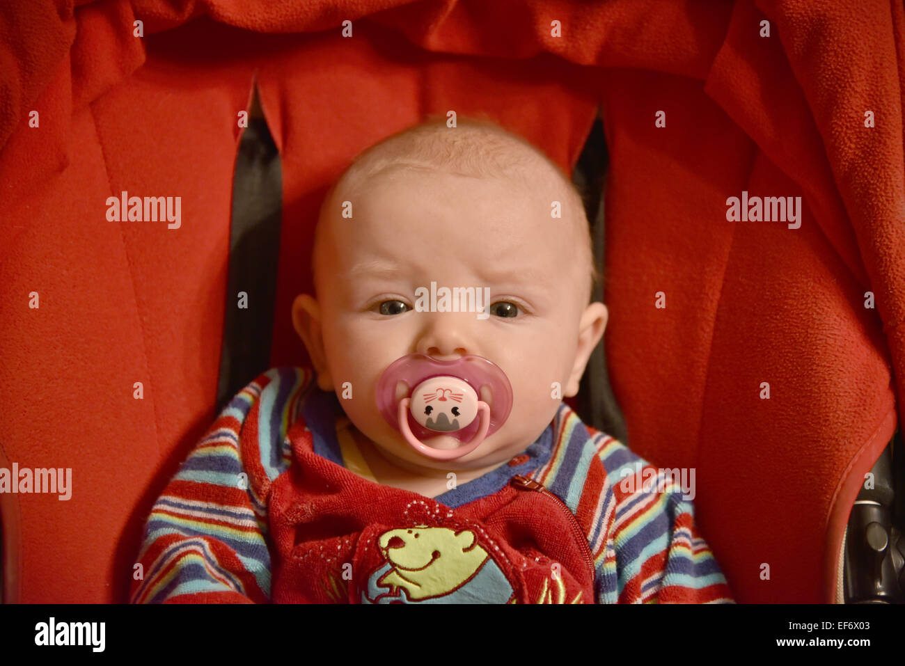 A baby girl with a dummy in her mouth - Stock Image
