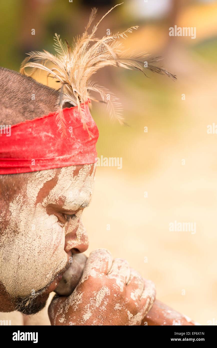 Close up of man playing the didgeridoo during a performance by Koomurri, an aboriginal dance group, Yabun Festival - Stock Image