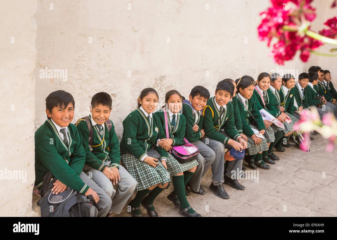 Local happy Peruvian schoolchildren in school uniform sitting on a bench having fun enjoying visiting Santa Catalina - Stock Image