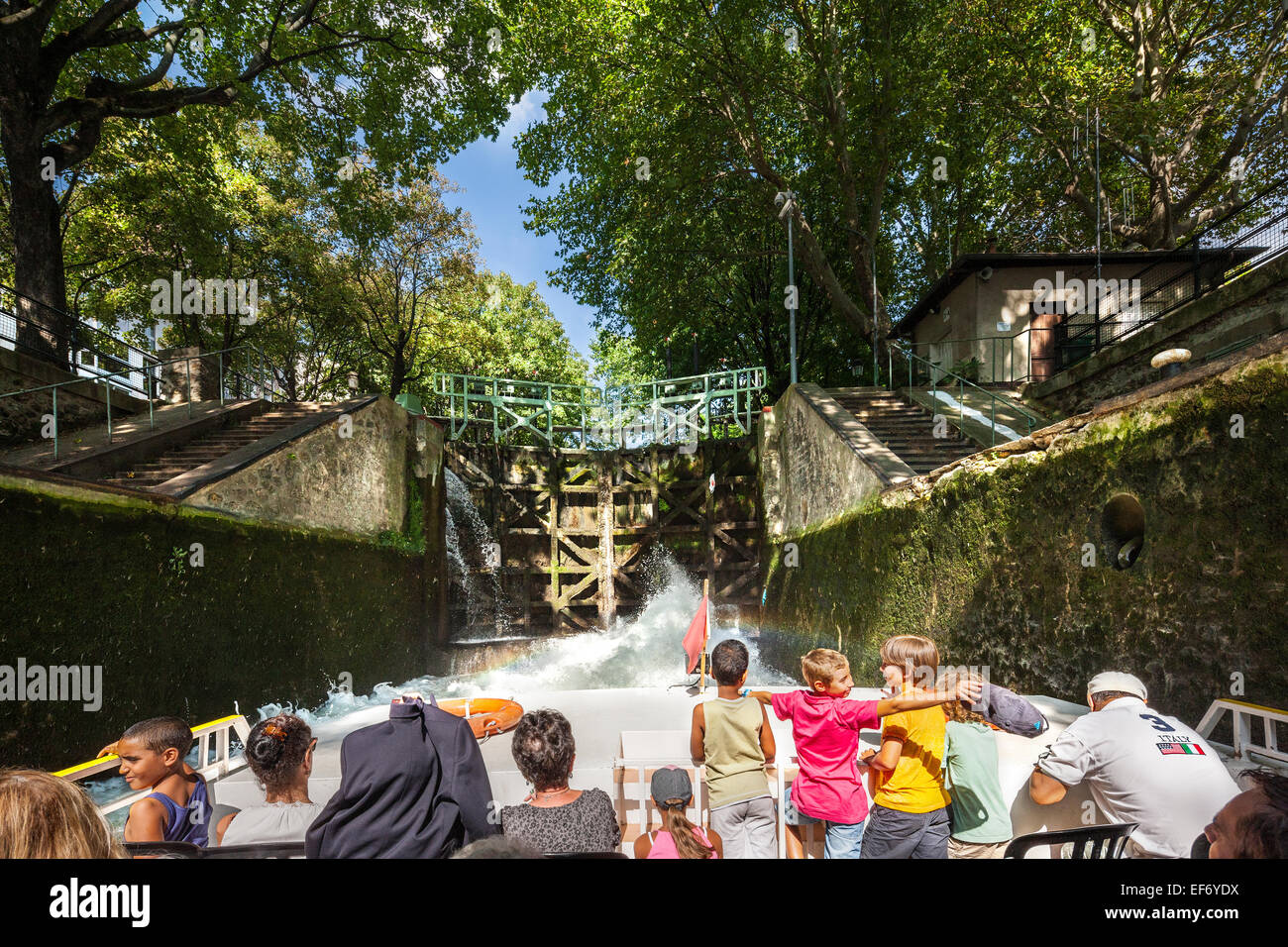Canal Saint Martin Paris. A tourist canal cruise boat in a lock with family, children watching, enjoying the water - Stock Image