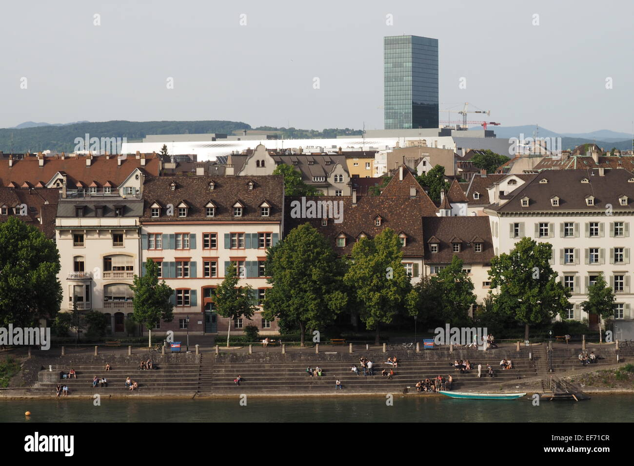 People sitting and sunbaking along the banks of the Rhine River in Basel. Stock Photo