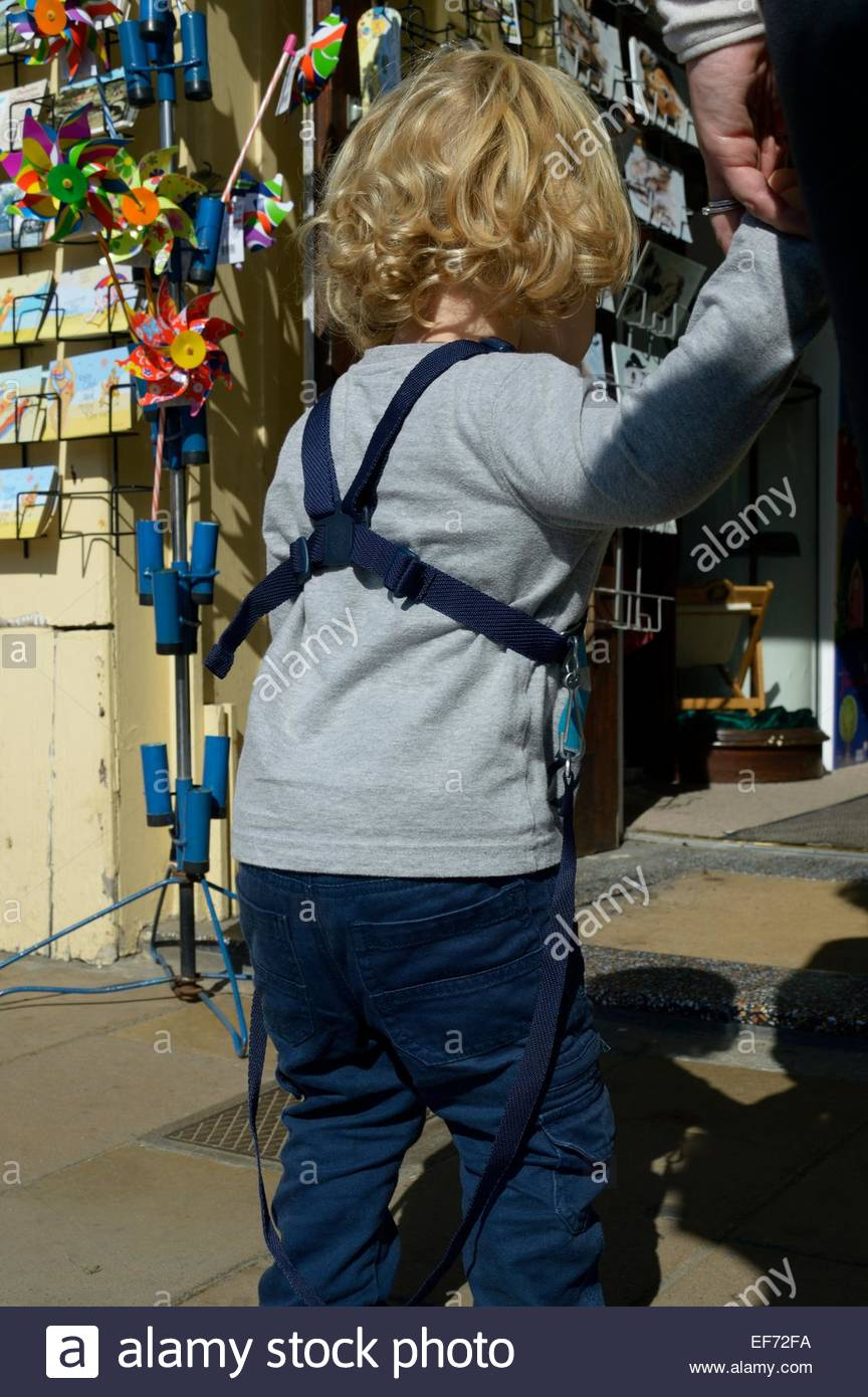Little boy in reins holding an adults hand whilst standing in a queue - Stock Image