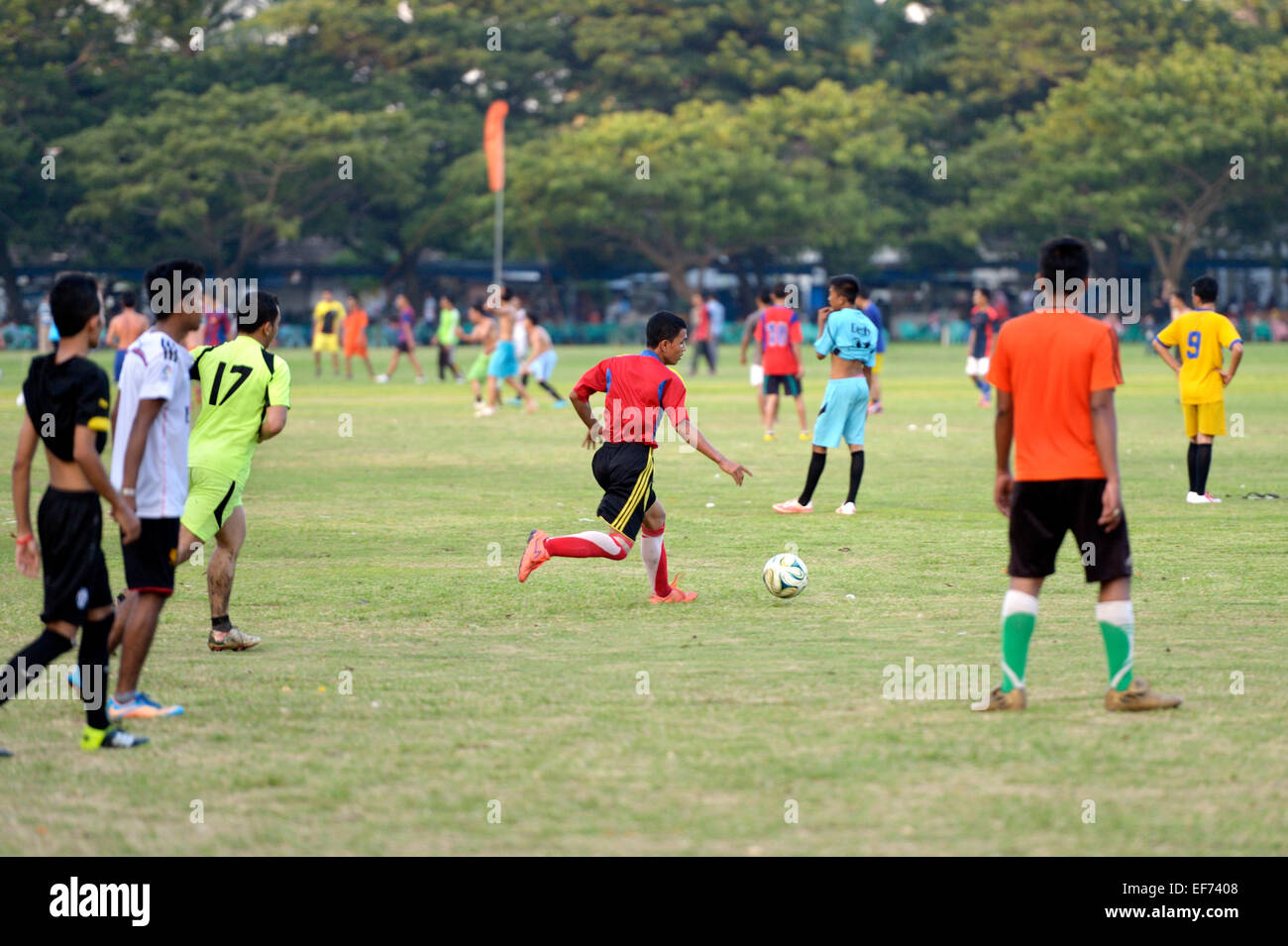 Teenagers playing football in a public park, Banda Aceh, Indonesia Stock Photo