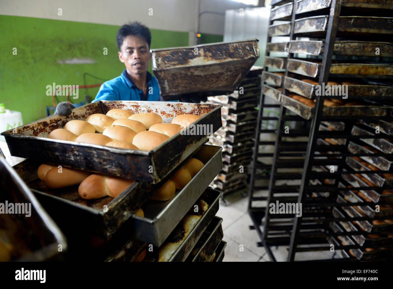 Young man in a bakery taking bread out of the oven, Gampong Nusa, Aceh province, Indonesia - Stock Image