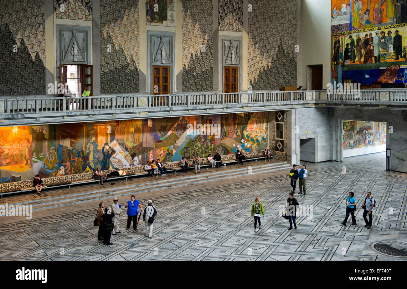 Visitors looking at the murals in the main hall of Oslo City Hall, Oslo, Norway - Stock Image