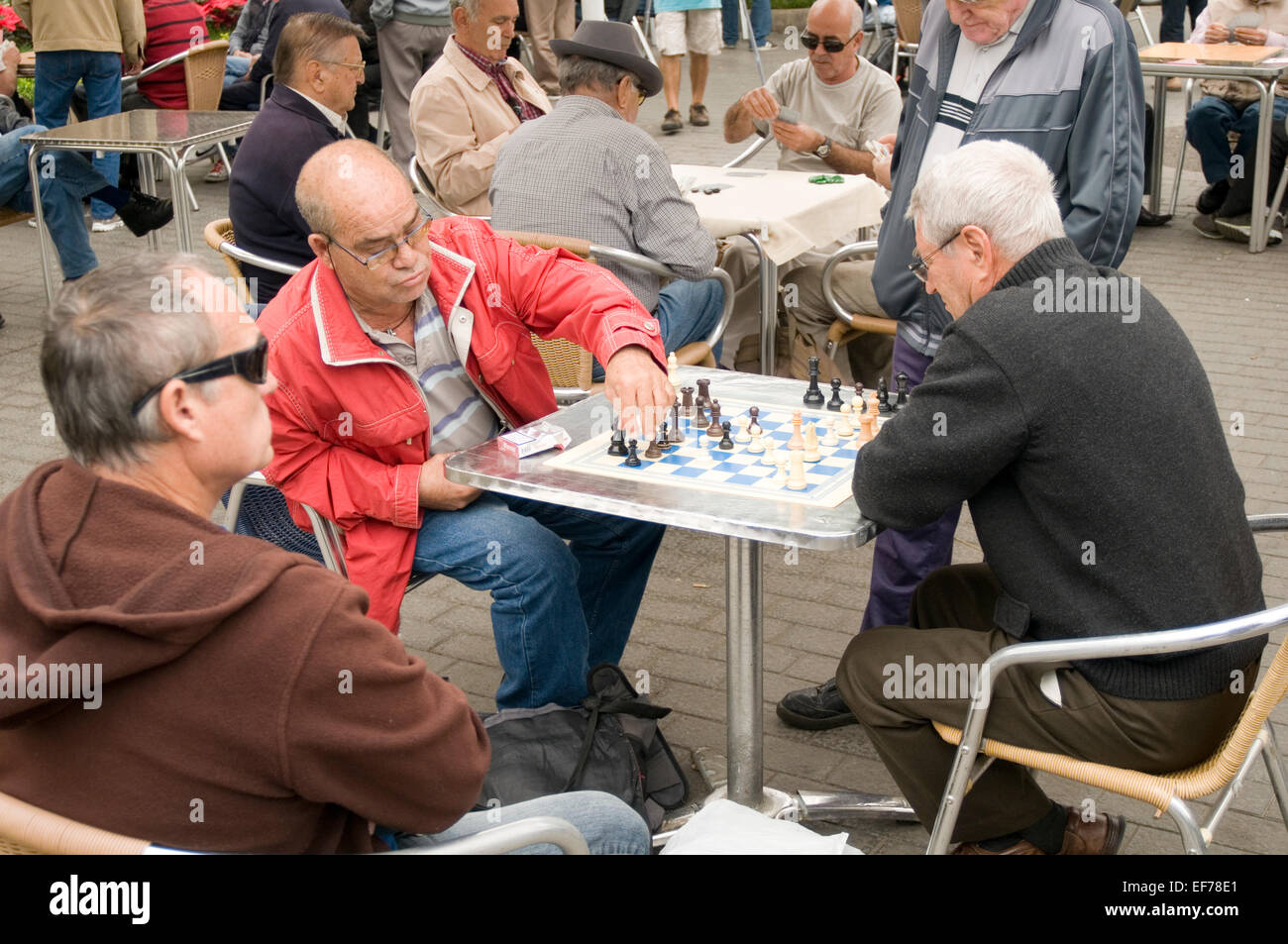 old men playing chess in a spainsh town square spain retirement retired activity gran canaria capital las palmas - Stock Image