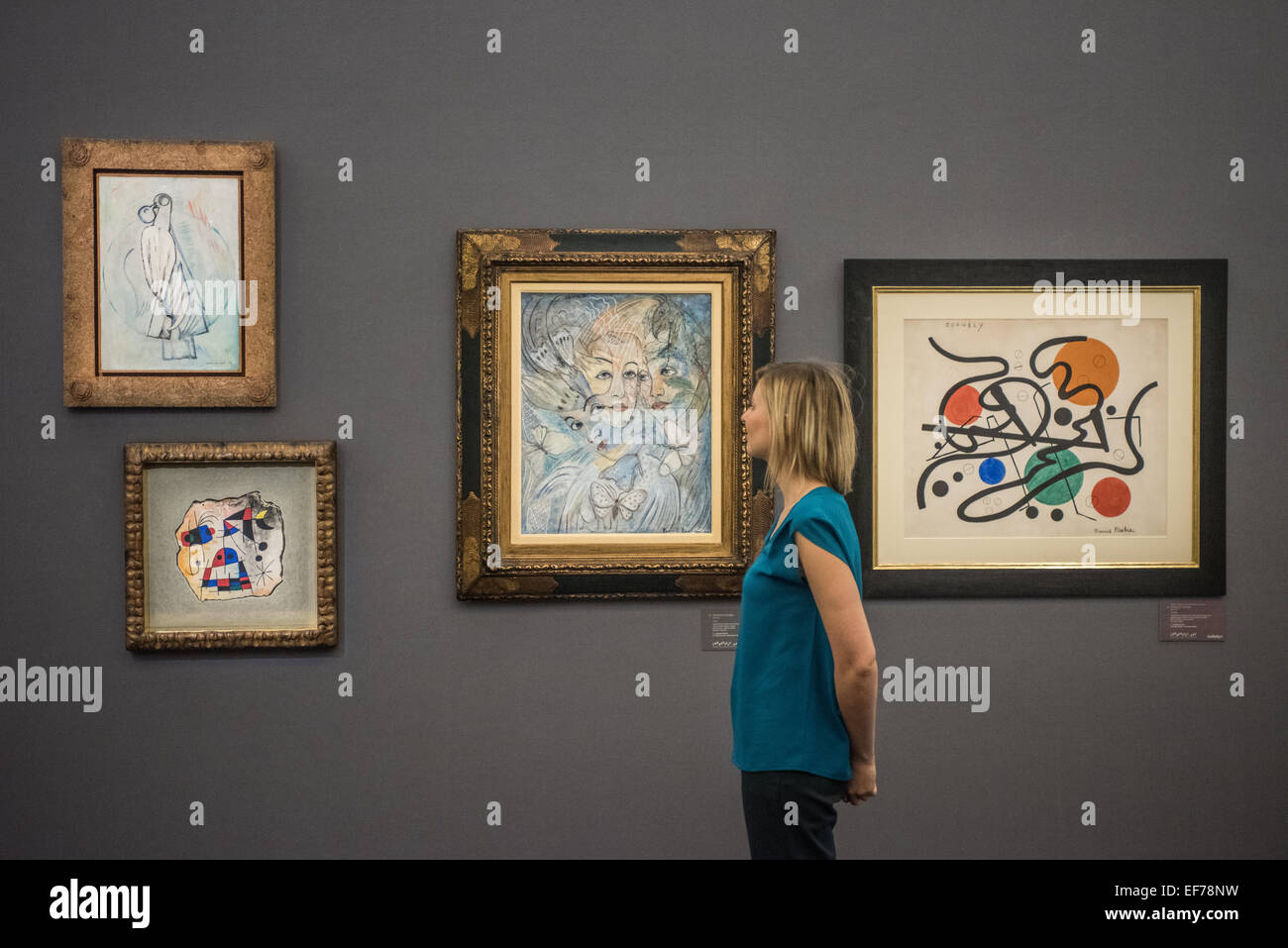 London, UK. 28th January, 2015. : a Sotheby's employee looks at Surrealist works by Max Ernst, Joan Miró and - Stock Image