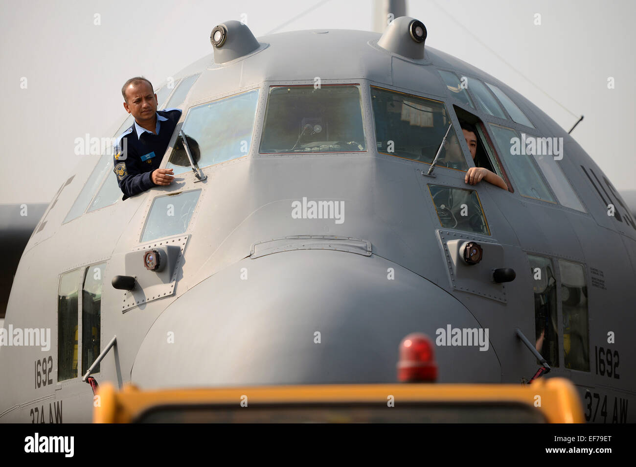 A Bangladesh Air Force airman and U.S. Air Force crew chief keep an eye on their USAF C-130H aircraft as it is towed - Stock Image