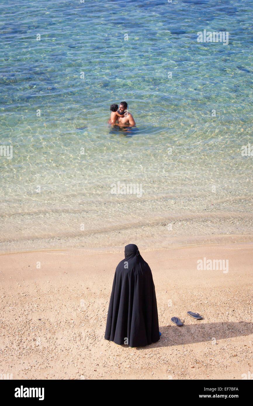MUSLIM MOTHER IN BURKA WATCHING HUSBAND AND CHILD SWIM Stock Photo