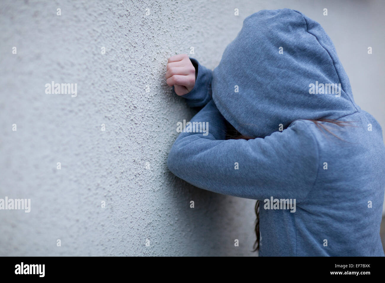 Sad child in hoodie with face hidden, leaning against a wall in despair - Stock Image