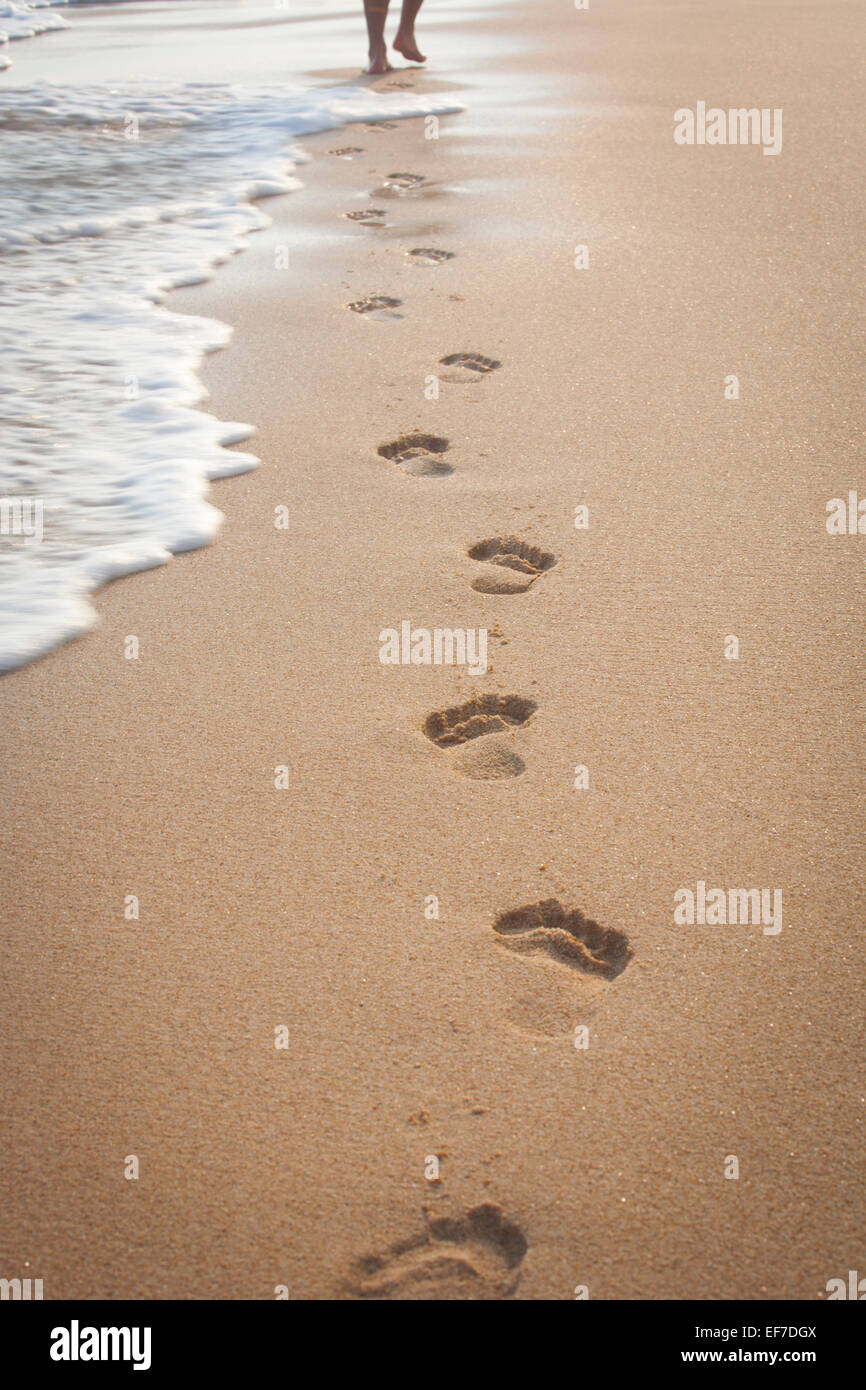 FOOTPRINTS IN THE SAND AND MAN'S FEET - Stock Image