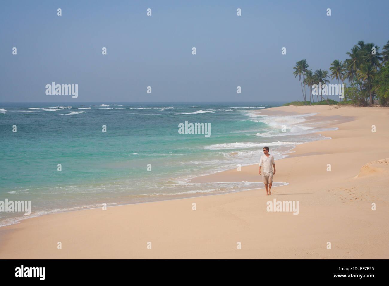 TOURIST ON DESERTED BEACH NEAR MIRISSA - Stock Image
