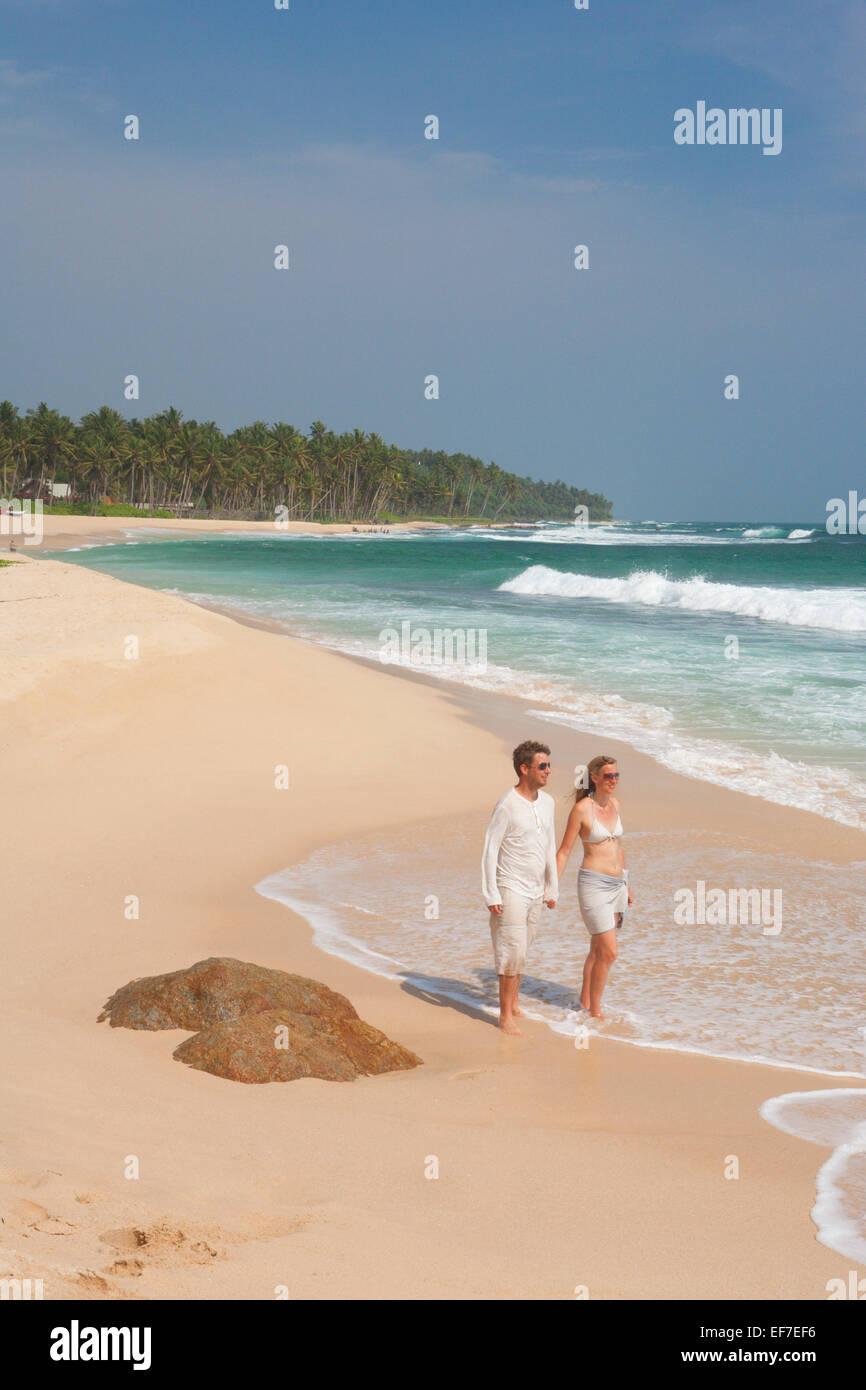 COUPLE ON DESERTED BEACH - Stock Image