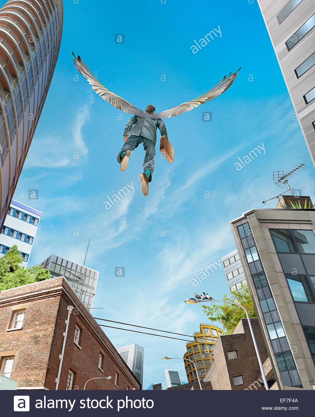 Successful businessman with wings flying over city - Stock Image