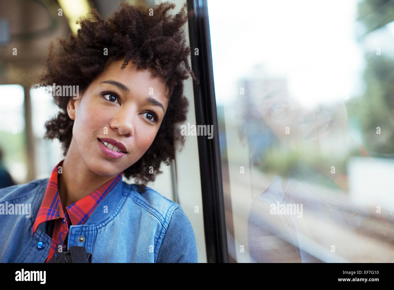 Daydreaming woman looking out train window - Stock Image