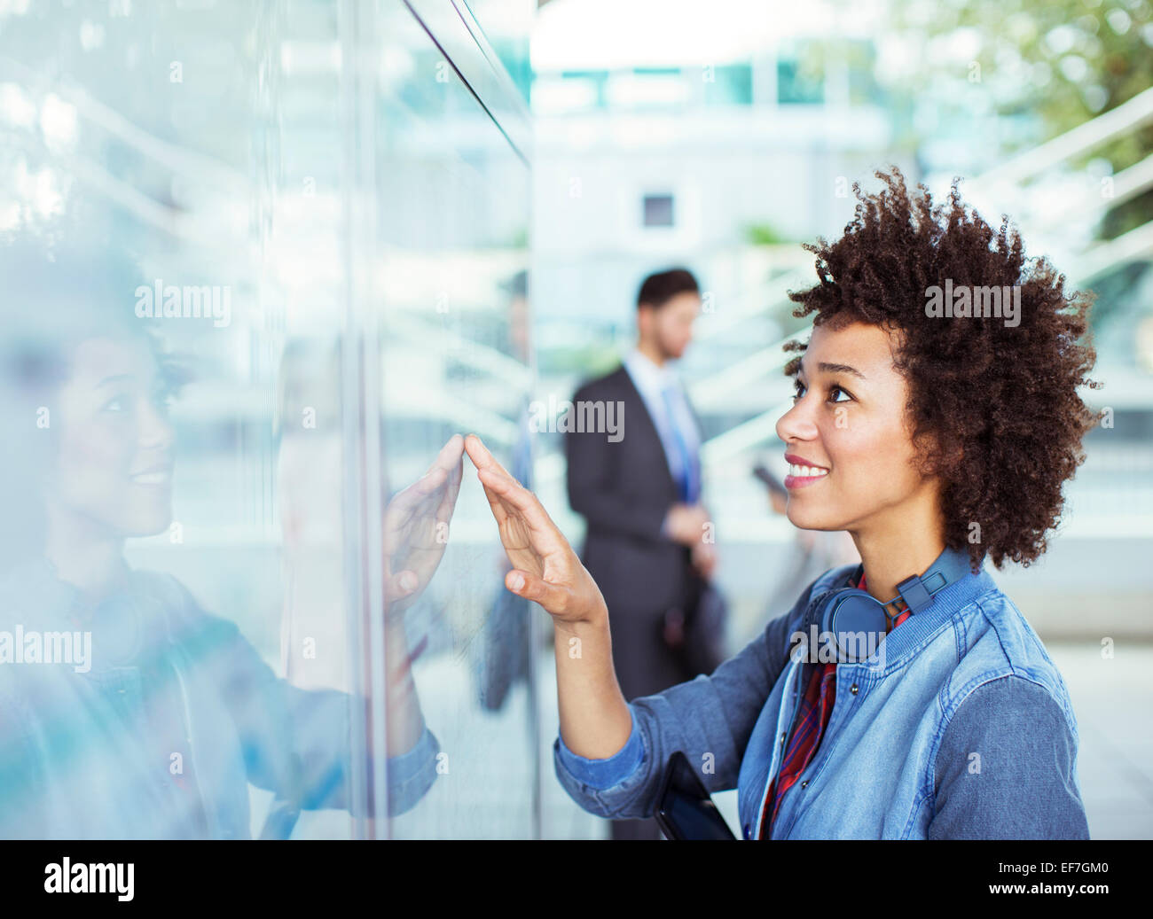 Woman reading transportation schedule at station - Stock Image