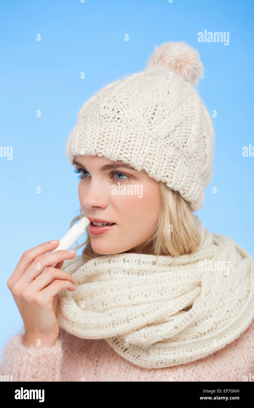 Female applying lip balm on her lips - Stock Image