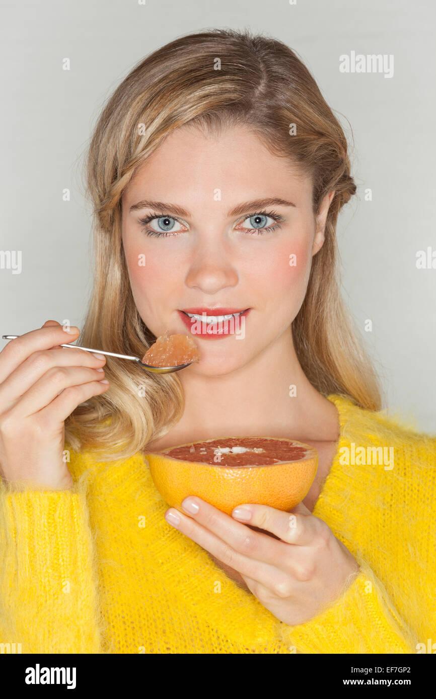 Portrait of a beautiful woman eating grapefruit - Stock Image
