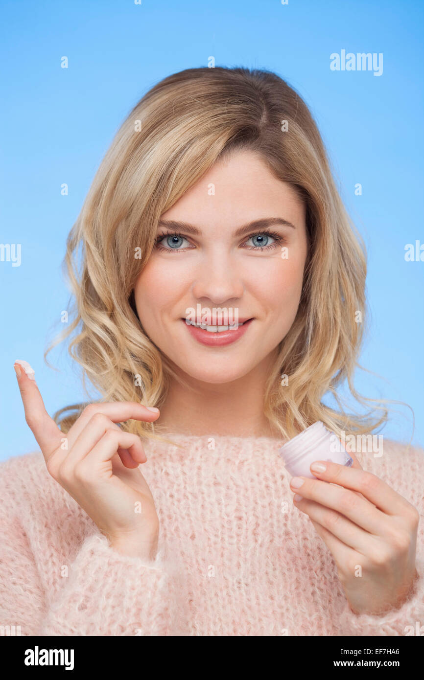 Close-up of a woman holding moisturizer cream - Stock Image