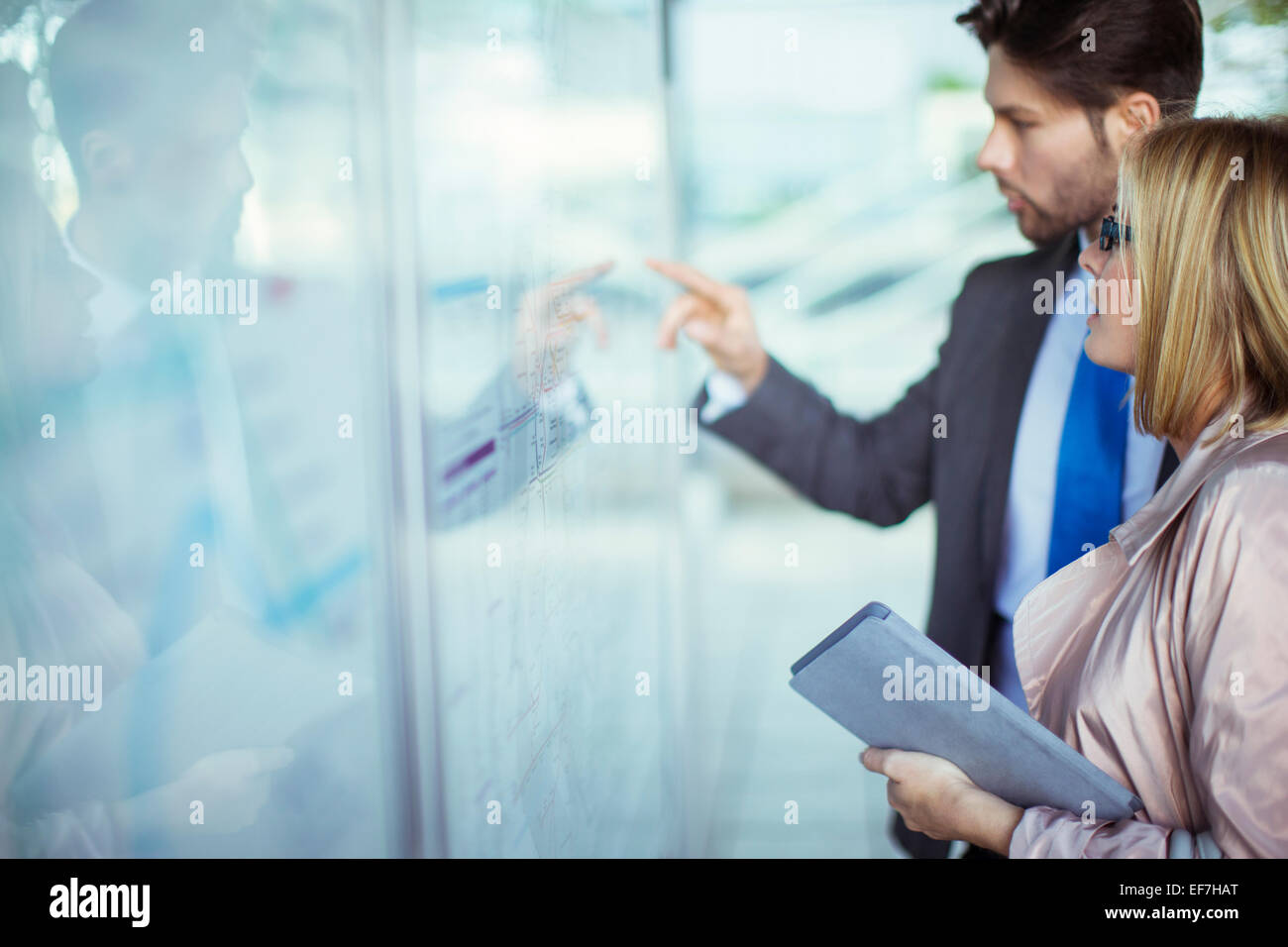 Business people reading transportation schedule at station - Stock Image