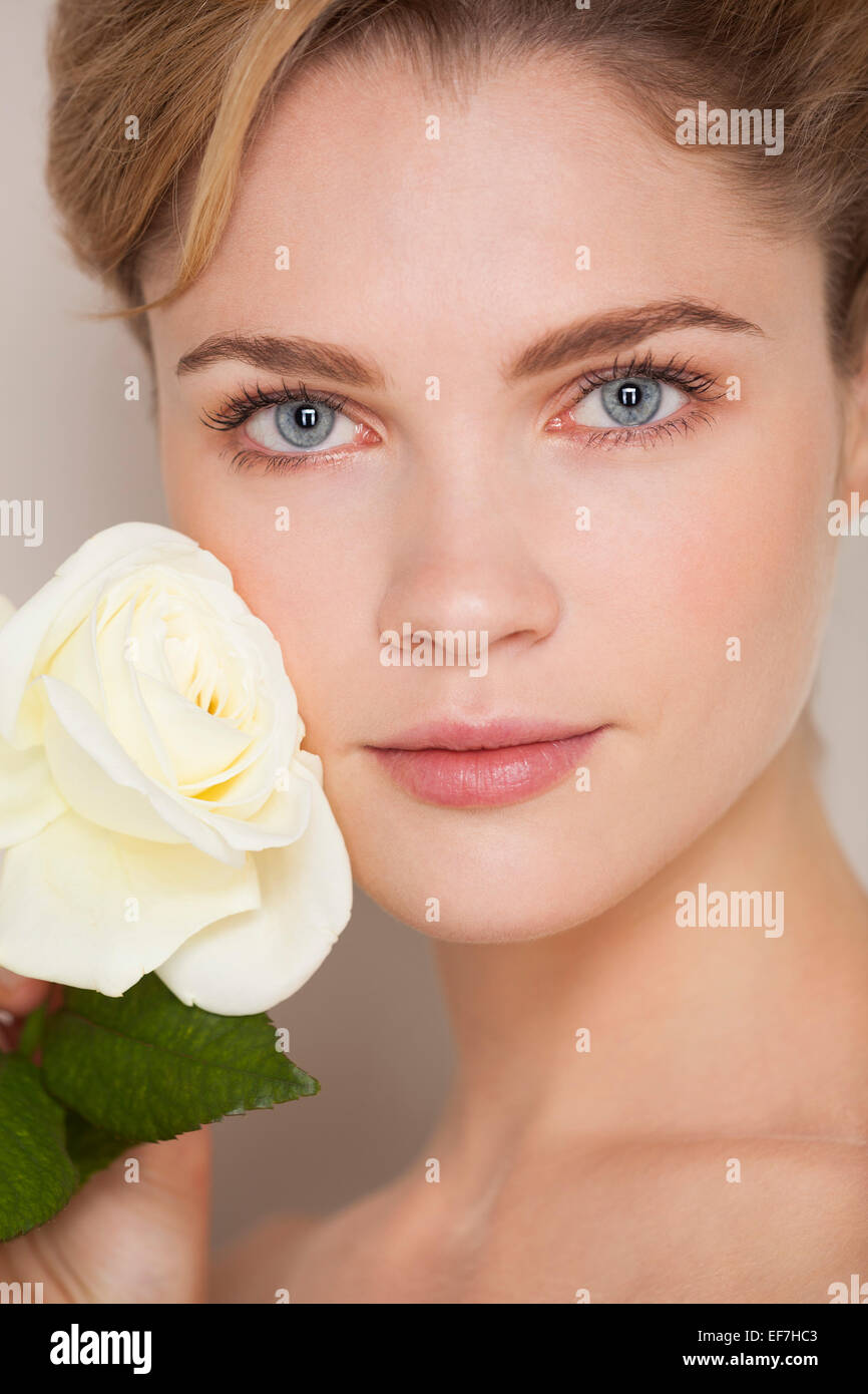 Beautiful woman touching rose on her face - Stock Image