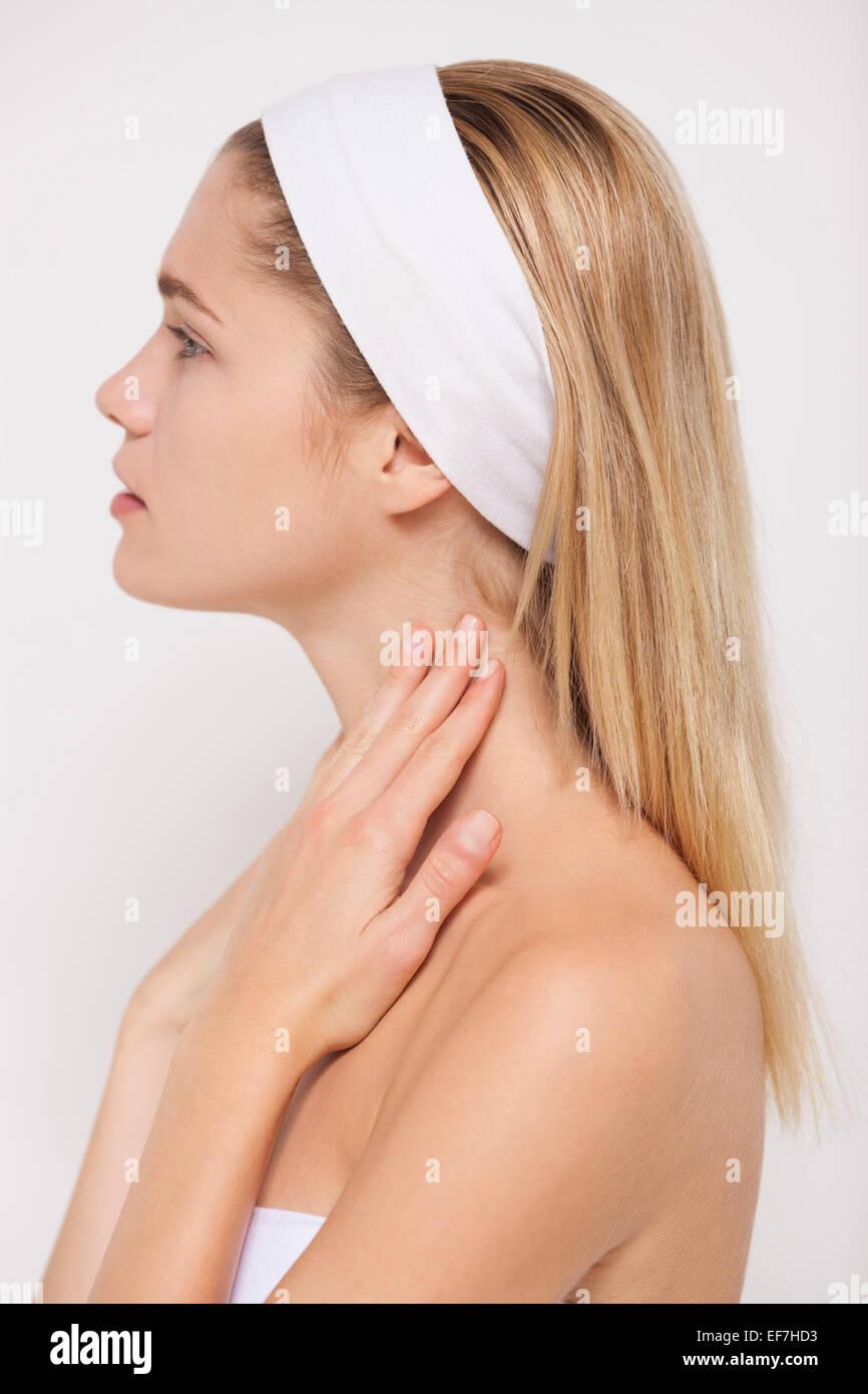 Beautiful woman applying moisturizer on her neck - Stock Image