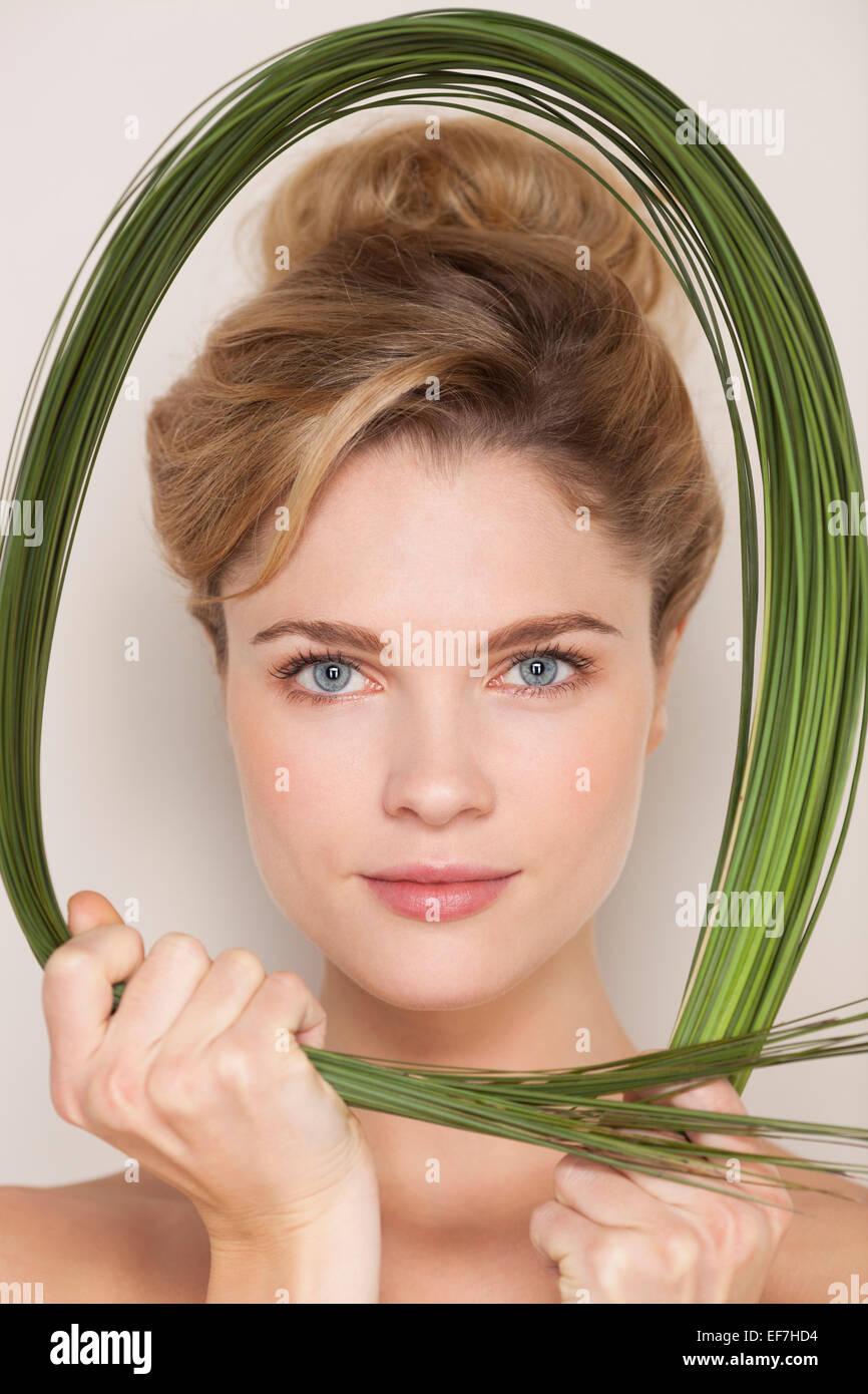 Portrait of a beautiful woman holding wheatgrass - Stock Image