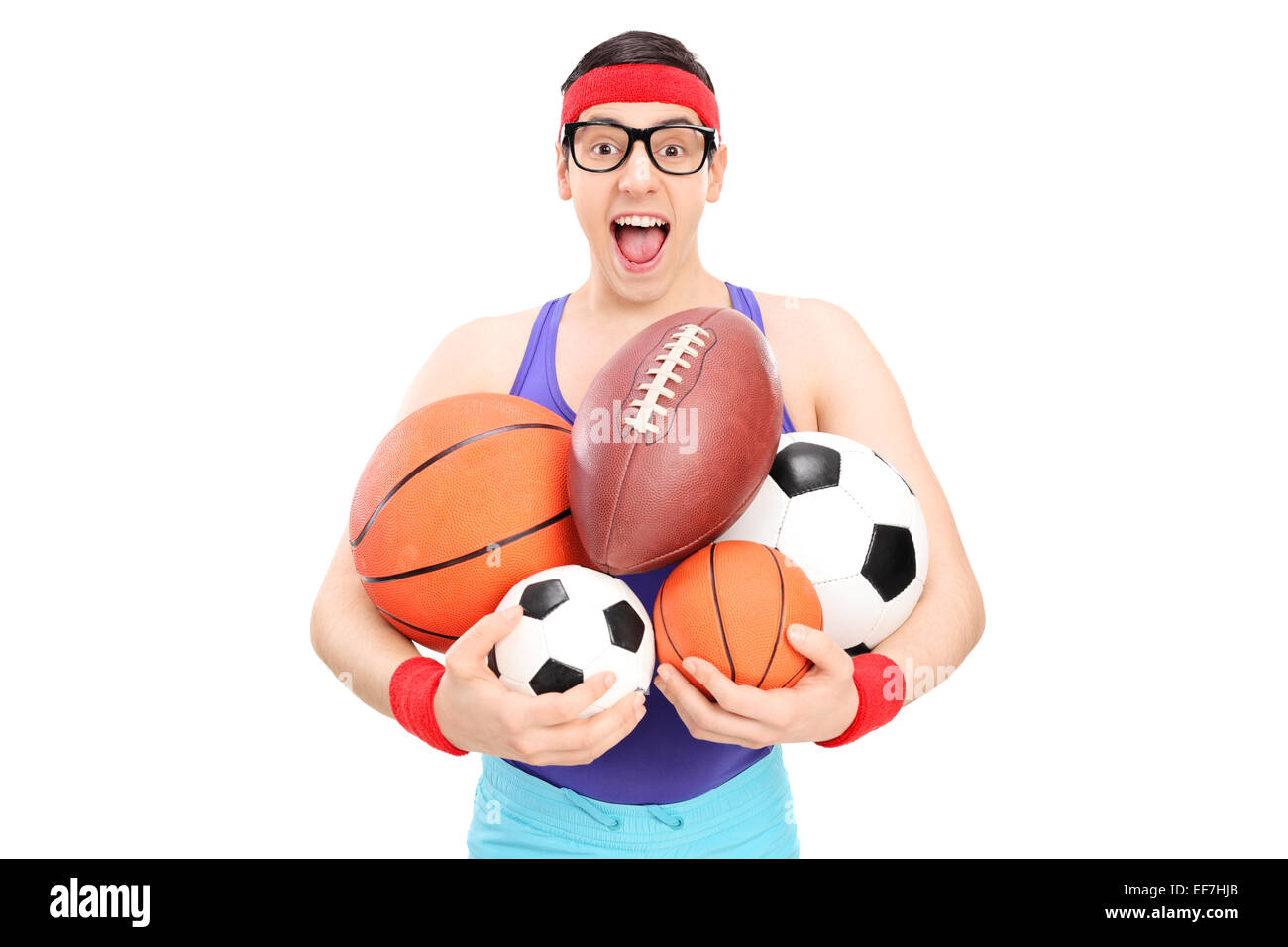 Nerdy guy holding a bunch of sports balls isolated on white background - Stock Image