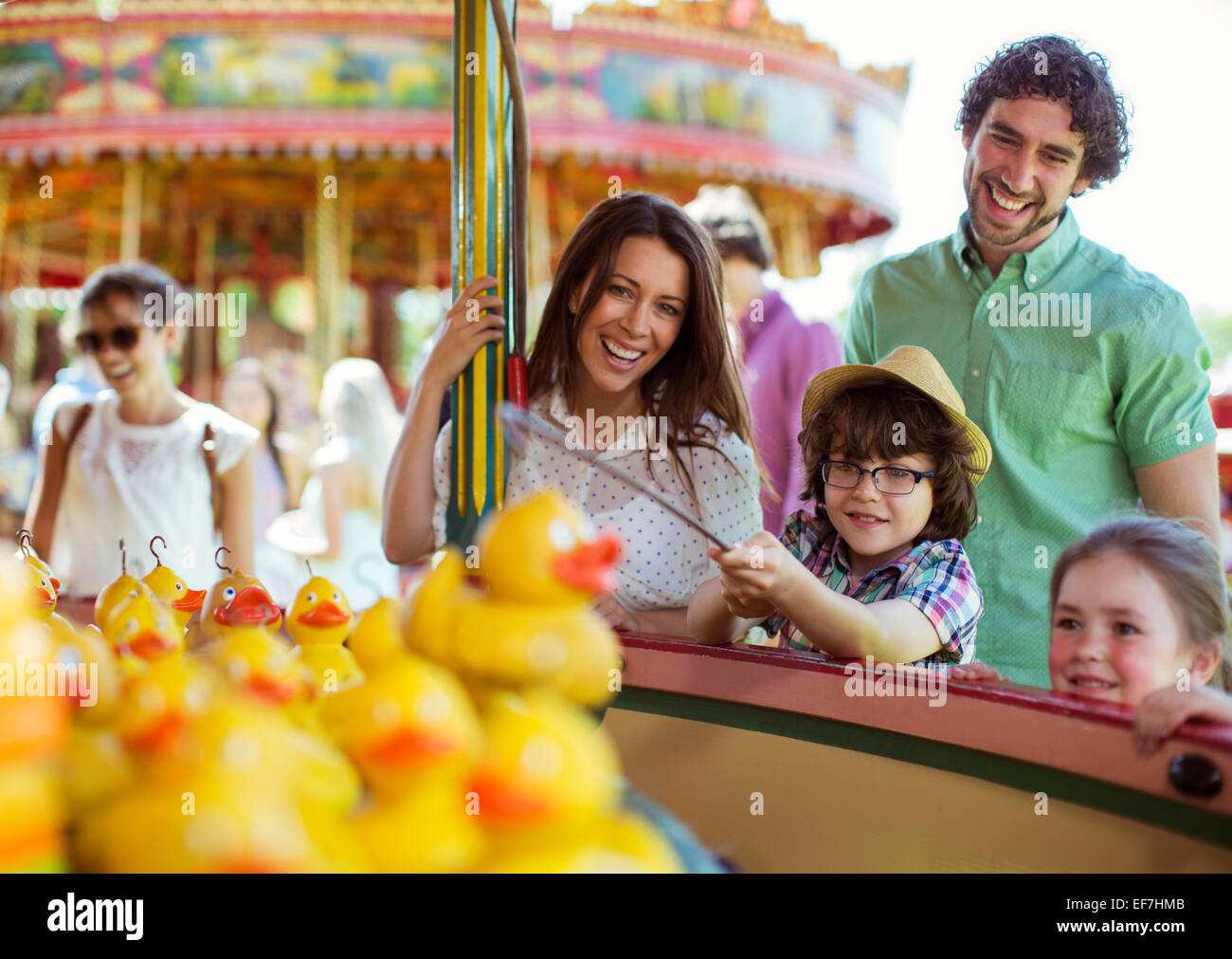 Parents with two children having fun with fishing game in amusement park - Stock Image
